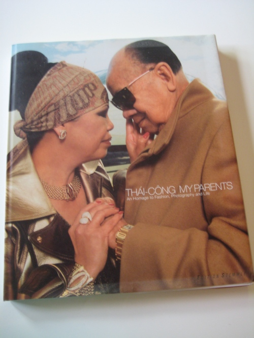 The cover of Thai-Cong's My Parents: An Homage to Fashion, Photography, and Life. His parents wear gold and camel Gucci, facing each other and holding hands tenderly.