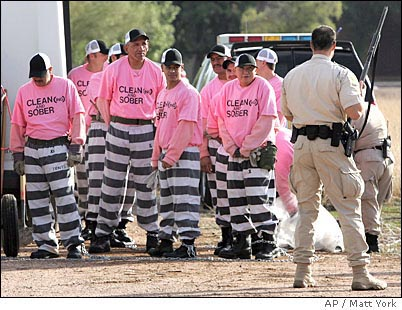 Sheriff Joe Arpaio reintroduces the black-and-white striped uniform in Arizona in 1997. Here prisoners in striped pants and pink t-shirts (for convictions of drunk driving) are chained together and watched over by armed sheriff's deputies.