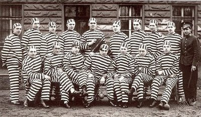 Prisoners in black and white stripes, posing for a photographer.
