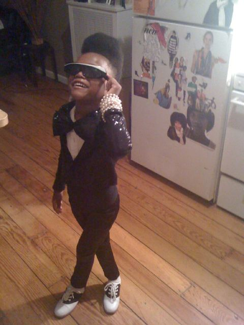 A very young black girl dressed up as Janelle Monae for Halloween.